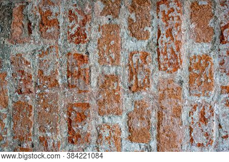 Wall Made Of Red Bricks Cleaned Of Plaster For Use In Illustration Design. Bricks Partially Covered
