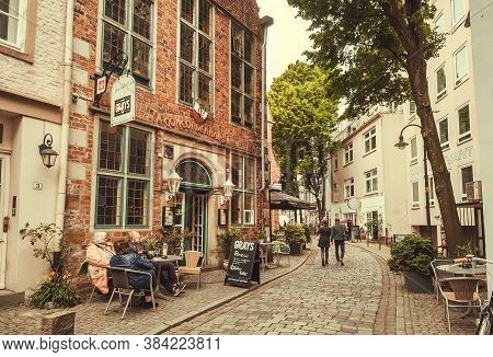 Bremen, Germany: Local Cafe On Narrow Street Of Historical Area With Some Visitors In Old Town On 25