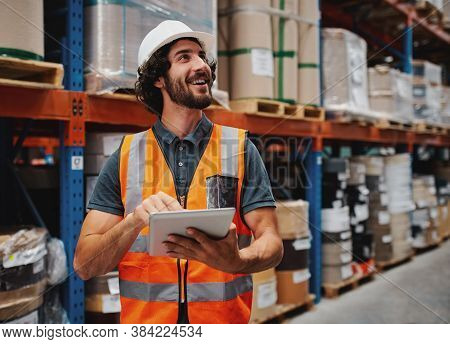 Waist Up Portrait Of Young Man Wearing Reflective Jacket Holding Digital Tablet Standing In Factory