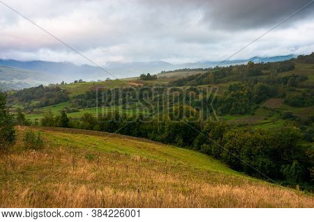 Rural Landscape In Mountain On A Cloudy Morning. Dramatic Hazy Scenery Of Carpathian Countryside