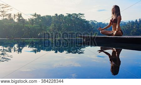 Good Morning With Yoga Meditating On Sunrise Background. Active Woman In Bikini Practicing At Villa