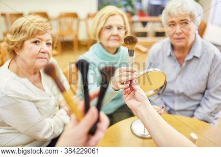 Make-up artist distributes make-up brushes to seniors in make-up advice in the retirement home