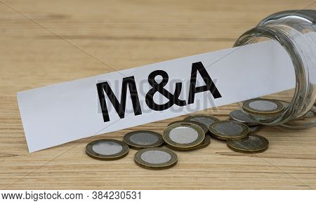 M$a (mergers And Acquisitions) - Word On Cubes On The Background Of A Capacity With Money. Business
