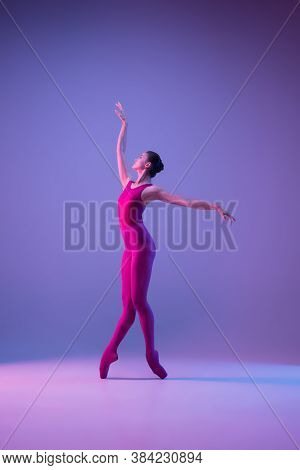 Dynamic. Young And Graceful Ballet Dancer Isolated On Purple Studio Background In Neon Light. Art, M