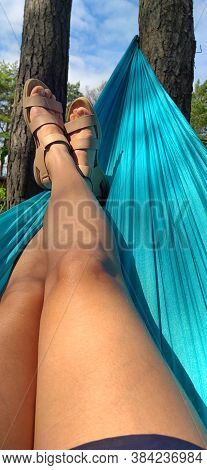 Crossed Legs Of A Woman Lying On A Hammock In The Woods.