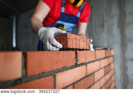 Builder Makes A Brickwork Of A Wall In An Apartment. A Man In Uniform Lays A Brick On Cement. Constr