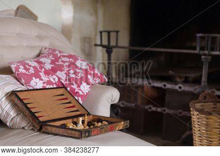 Still life interior with old fireplace and antique backgammon game