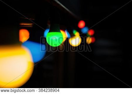 Coloured bulbs bokeh background with space for text. Festive string of lights in green, yellow, blue and red, suitable for holiday or Christmas themed images.