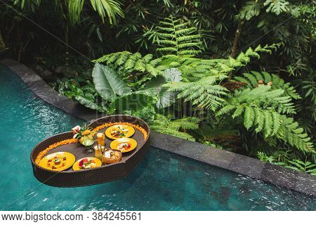Floating Breakfast In Jungle Swimming Pool, Tropical Resort. Black Rattan Tray In Heart Shape, Valen