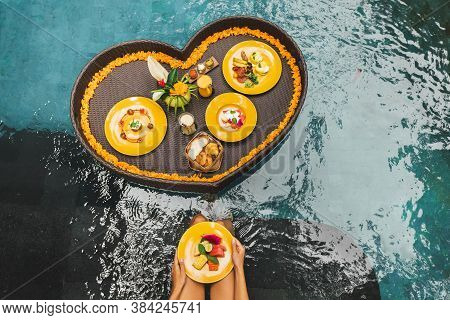 Floating Breakfast In Pool. Woman Hands Holding Plate With Fresh Fruits. Summer Healthy Food Diet. T