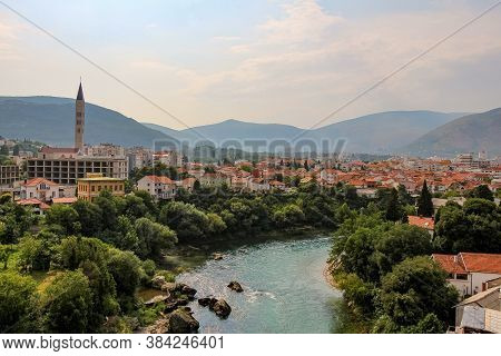 The Neretva River Upstream Of The Arched Old Bridge In Mostar, With A Mosque And Mountains In The Ba