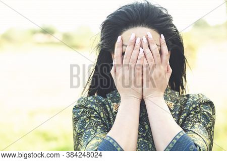 Beautiful Girl Covers Her Face With Her Hands.