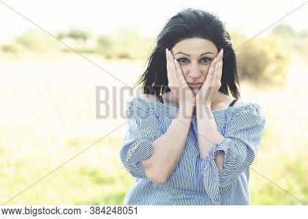 Happy Beautiful Girl Holding Cheeks Laughing Looking At Camera.