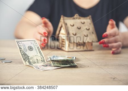 Saving Money For House And Real Estate. Woman Hand Protecting On Stack Coins And House Model On Tabl