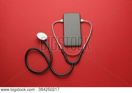 Smartphone And Stethoscope On Red Background. Online Medicine (telemedicine) Technology. Service For