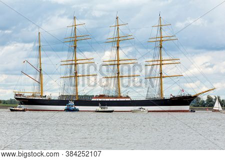 Hollern-Twielenfleth, Germany - September 7, 2020: Historic barque PEKING moored on Elbe river waiting to be towed to German Port Museum at Hamburg, accompanied by other  vessels with spectators