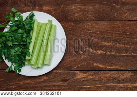 Cut Celery Stalks And A Bunch Of Green Parsley In A White Plate On A Brown Wooden Background Top Vie