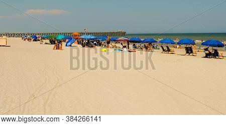 Richmond Va - June 22, 2020 - Summertime Beachgoers Under Blue Umbrellas On June 22, 2020 In Myrtle