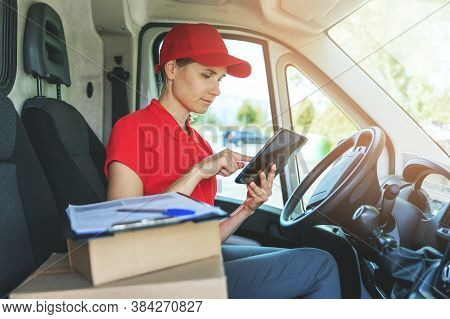 Delivery Woman Using Digital Tablet While Sitting In Van