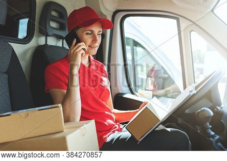 Delivery Woman Talking On Mobile Phone In Van