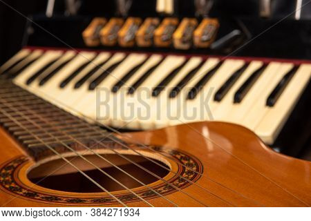Old Accordion And A Beautiful Guitar Composing A Scene On A Rustic Wooden Surface With Black Backgro