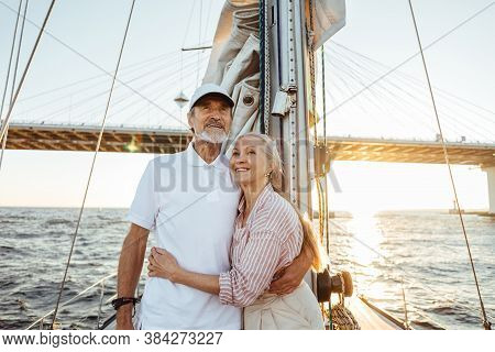 Happy Couple Of Two Mature People Enjoying Holidays On Private Yacht. Smiling Seniors Hugging Togeth