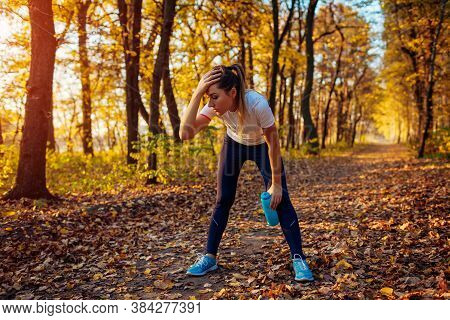 Runner Having Rest After Workout In Autumn Forest. Tired Woman Holding Water Bottle. Sportive Active