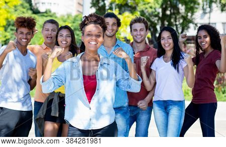 Pretty African American Female Student With Group Of Cheering Young Adults Outdoor In Summer In City