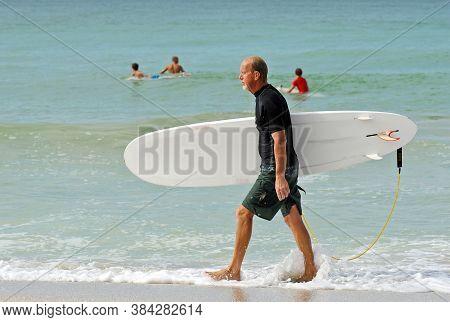 An Older Surfer On The Beach