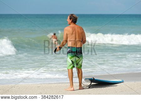 An Older Man With Surf Board