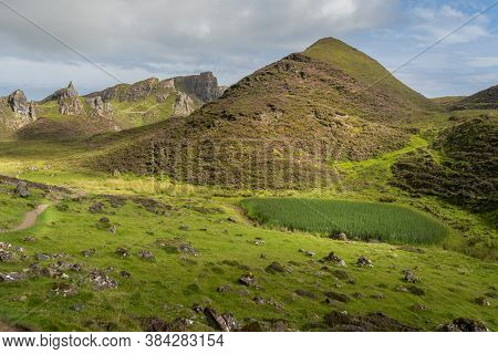 Scenic View Of Rock Formations In Quiraing, Isle Of Skye, Scotland. Grassy Mountains Covered By Bloo