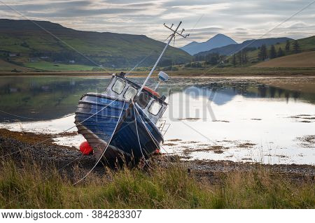 Old Boat Abandoned On A Loch Coastline In Scotland. Concept Of Sadness And Loneliness