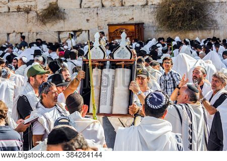 JERUSALEM, ISRAEL - SEPTEMBER 26, 2018: The Jews, wrapped in tallits, pray at the Western  Wall. Sukkot. Religious Jews carry out sacred Torah Scrolls. Religious tourism concept.