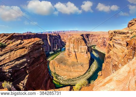 Horseshoe Bend is a beautiful meander of the Colorado River. USA, Arizona, Glen Canyon Recreation Area. Deep canyon of red sandstone. Concept of active and photo tourism