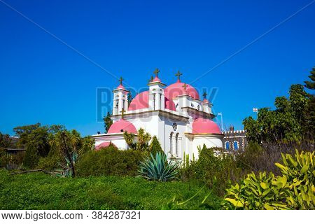 Snow-white church with pink domes and golden crosses. Orthodox monastery of the Twelve Apostles. Gorgeous green south park. Israel. The concept of religious pilgrimage and photo tourism