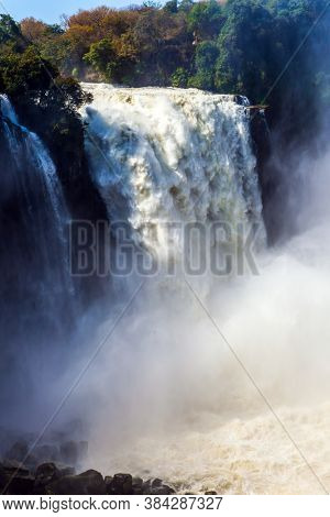 The Victoria Falls located on the Zambezi River. Giant cloud of water fog over waterfall. Victoria National Park. Journey after the wet season. Concept of extreme and photo tourism