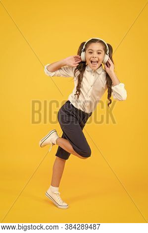 A Perfect Song For Active Child. Happy Little Girl Moving Active To Music. Active Schoolchild Runnin