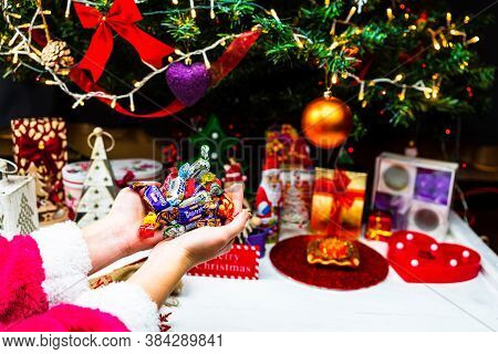 Hand Holding Chocolate Candies In Front Of The Christmas Tree. Decorating Christmass Tree Or Unpacki