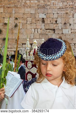Handsome little boy with blond side curls and blue eyes, in skullcap. Western Wall of the Temple. The Jews brought the Torah Scroll for prayer. Autumn Jewish holiday Sukkot