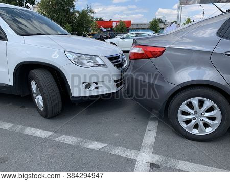 Two Cars Next To Each Other. Cars Are Parked Very Close. Small Clearance From Bumper To Bumper.