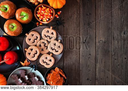 Rustic Halloween Treat Side Border Over A Dark Wood Background With Copy Space. Top View. Variety Of