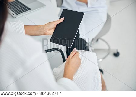Woman With A Gadget Having A Consultation With A Cosmetician