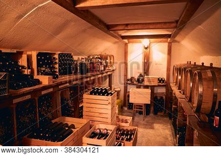 Storage Room With Wine In Bottles And Barrels.