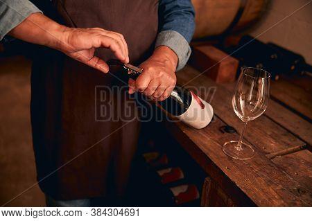 Winemaker In Apron Opening Bottle Of Wine