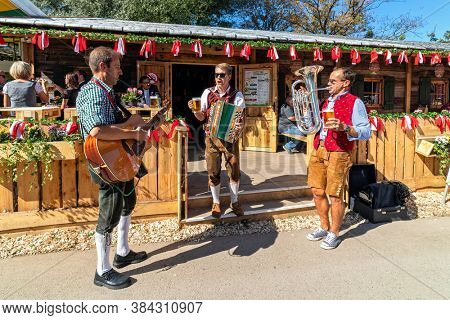 VIENNA, AUSTRIA - SEPTEMBER 28, 2018: Music band performing while people drinking beer during famous traditional Oktoberfest (aka Wiener Wiesn-Fest) taking place each year in Vienna, Austria.