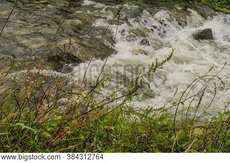 Water In River After Monsoon Rain Flowing Rapidly Over Boulders.