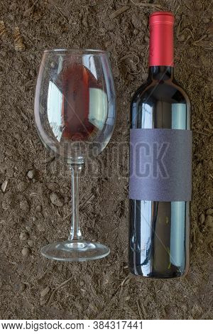 Wine Bottle Mockup Next To A Red Wine Glass