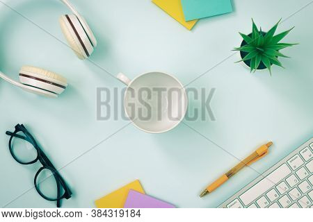 Center Coffee Cup And Office Supplies As Keyboard Headphone Pen Stick Note Office Plants And Glasses