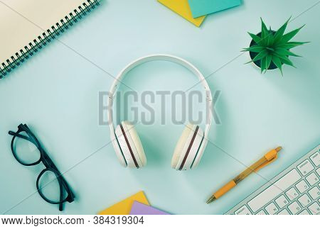 Headphone At Center And Office Supplies As Keyboard Pen Stick Note Office Plants Glasses And Spiral