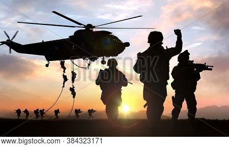 Silhouette  Of Military Operation At Sunset With  Helicopter In Background